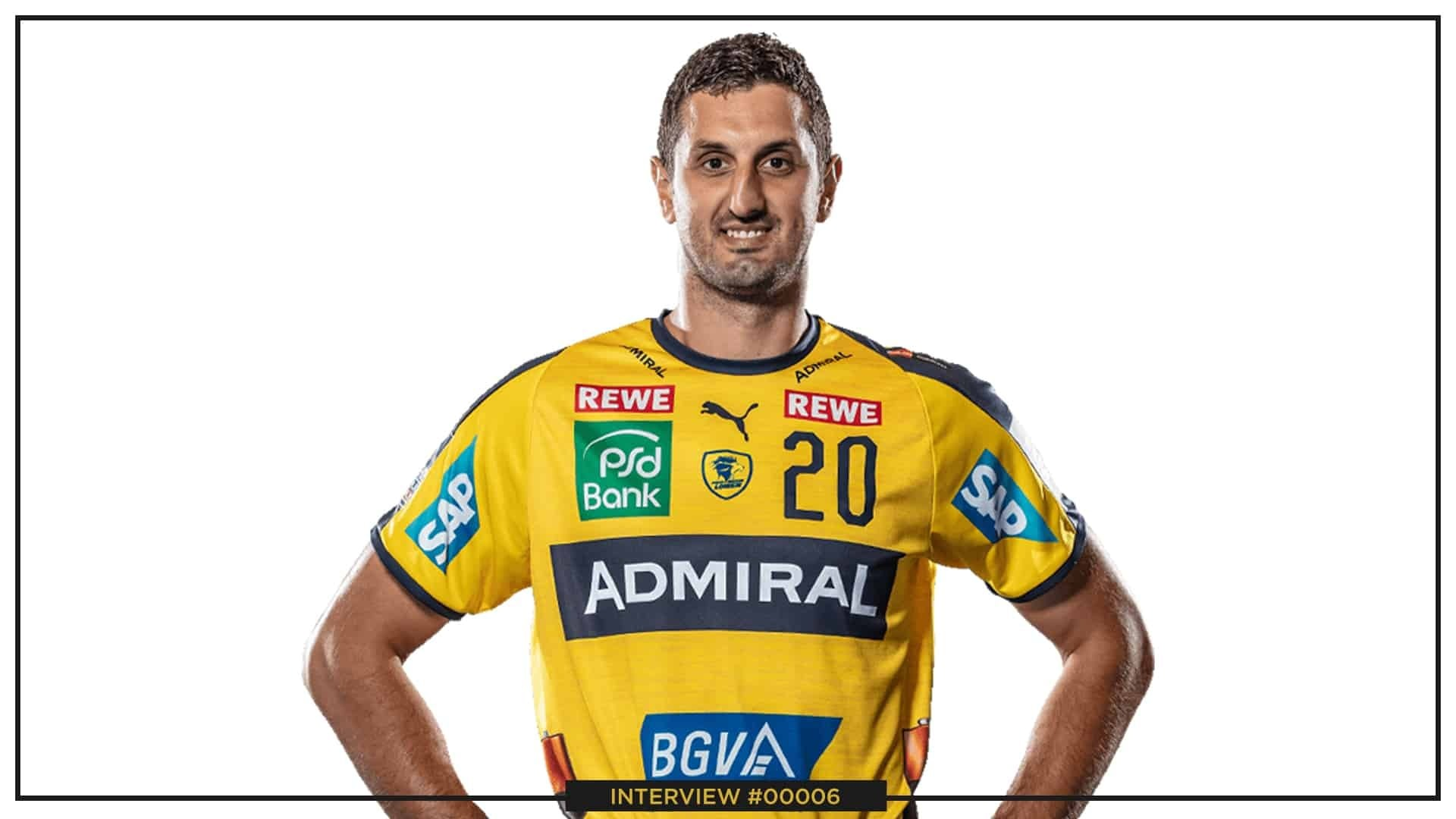 Ilija Abutovic wearing his jersey in a yellow colour and smiling while staring in front of the camera on a white background.