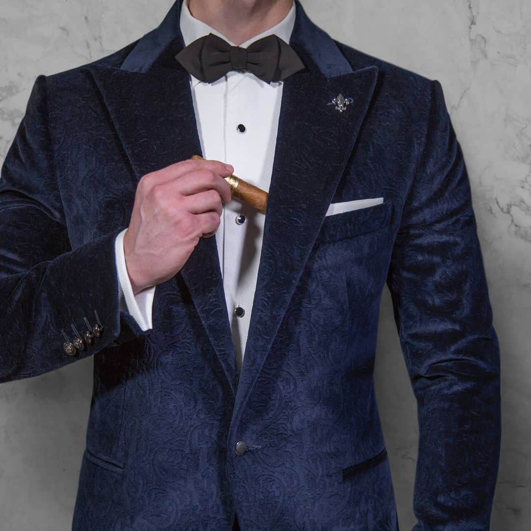An image of a man putting his cigar in the pocket of his blue suit. He is also wearing a white Signori shirt, and a black bow tie. His head is not visible.