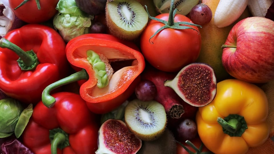 An image of fruits and vegetable including apple, banana, fig, kiwi, tomato and pepper.