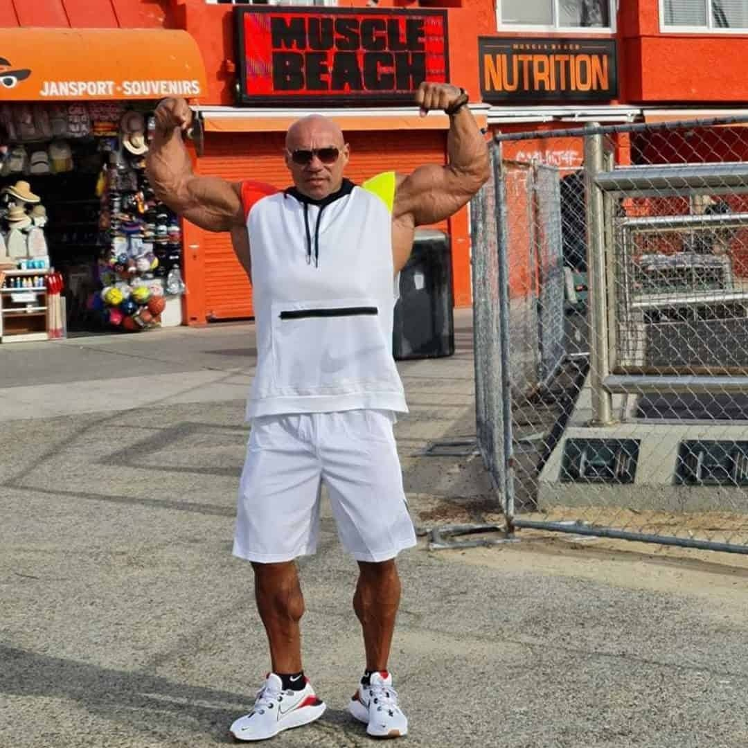 Tose Zafirov flexing his muscles at the Muscle Beach. He is wearing white t-shirt with orange and yellow details, white shorts, and sunglasses on his eyes.