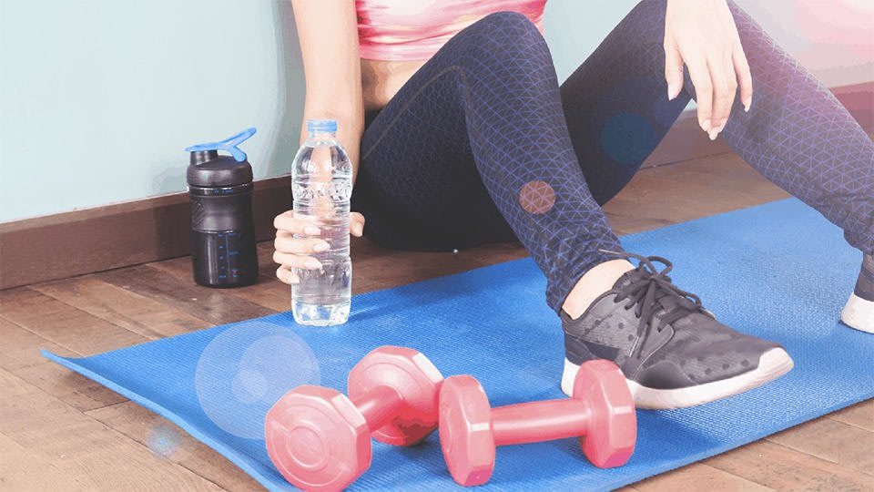 A woman holding a plastic bottle of water next to dumbbells, we can't see her face, the focus is on her legs.