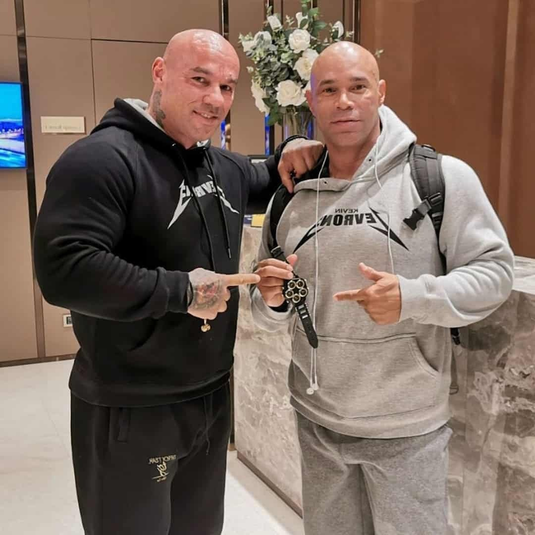 An image of Tose Zafirov giving his favorite watch to Kevin Levrone as a sign of respect. They're staying one to another, pointing to the watch. Tose is wearing black hoodie and Kevin is wearing grey hoodie from his brand