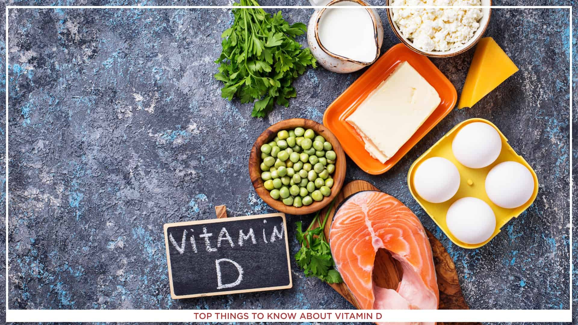 An image of salmon, eggs, cheese, milk, and other things containing vitamin D, on a dark grey background, togehter with a table with vitamin ''D'' on it.