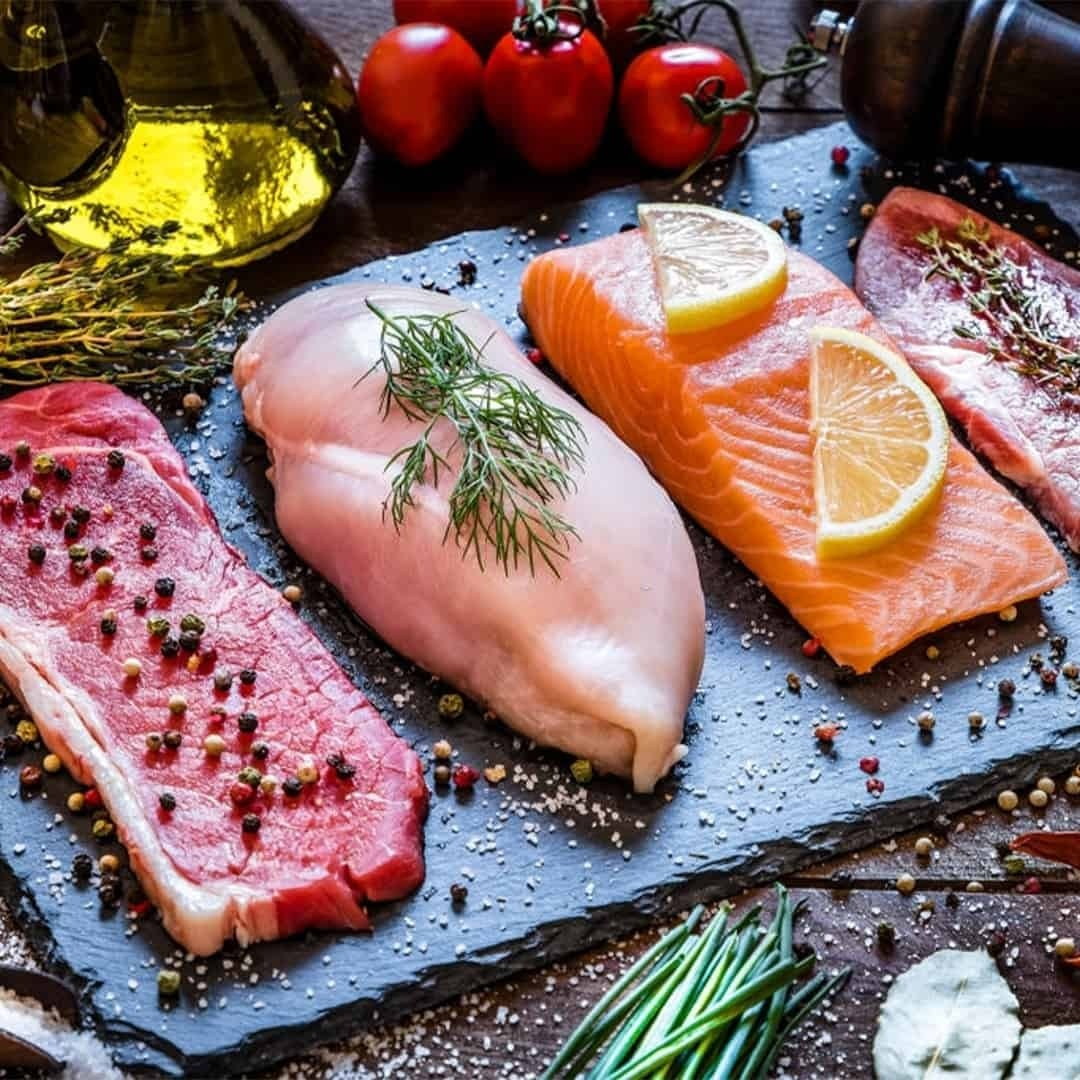 An image of steak, chicken meat and salmon with lemon on it that are not grilled, on a plate . There are also Cheri tomatoes and olive oil on the image