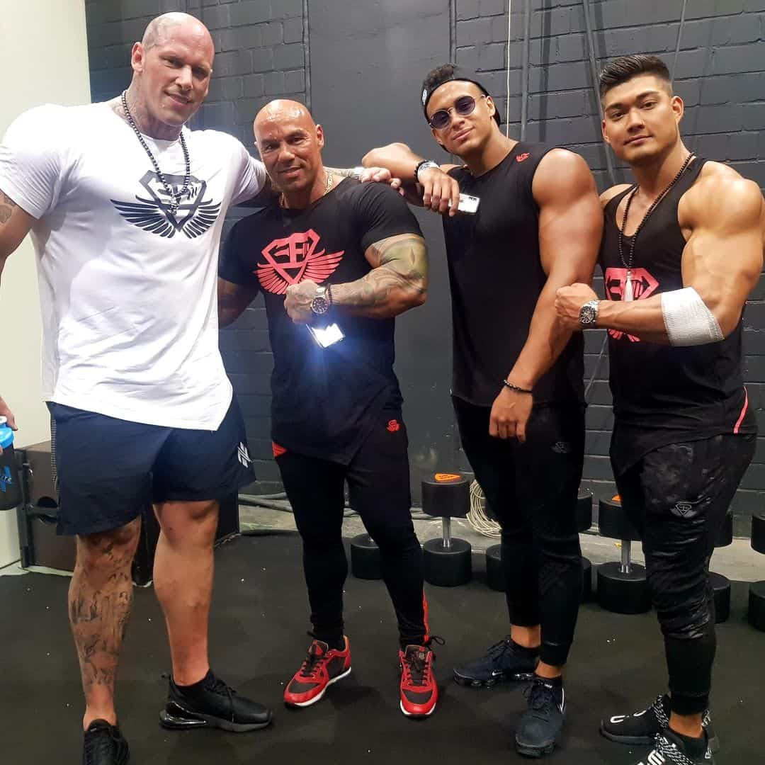 Tose Zafriov standing next to some other bodybuilders. He is wearing black t-shirt with red logo, and black sweatpants, with black sneakers with red details.