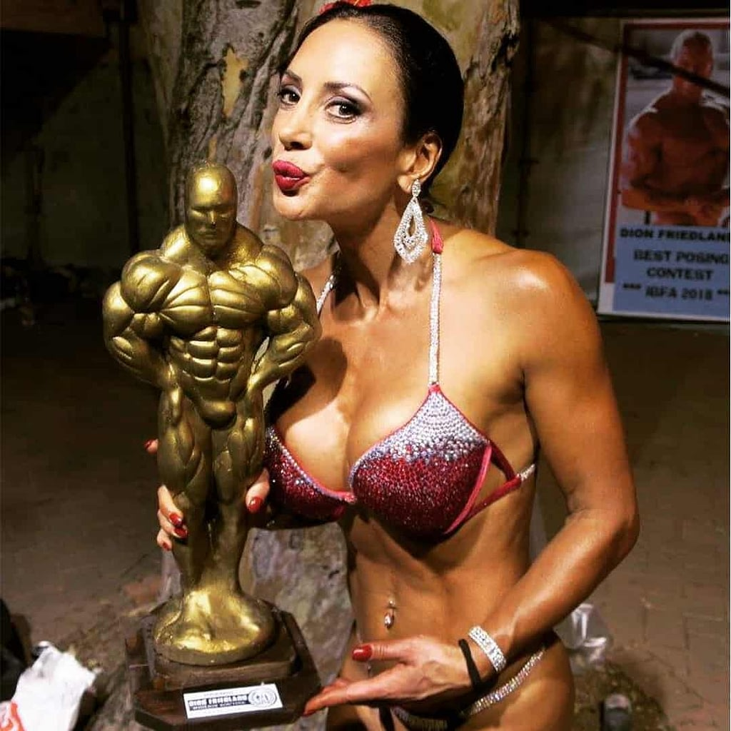 An image od Angelina Friedland after a competition with a goblet in her hands. She is wearing red elegant bikini set.