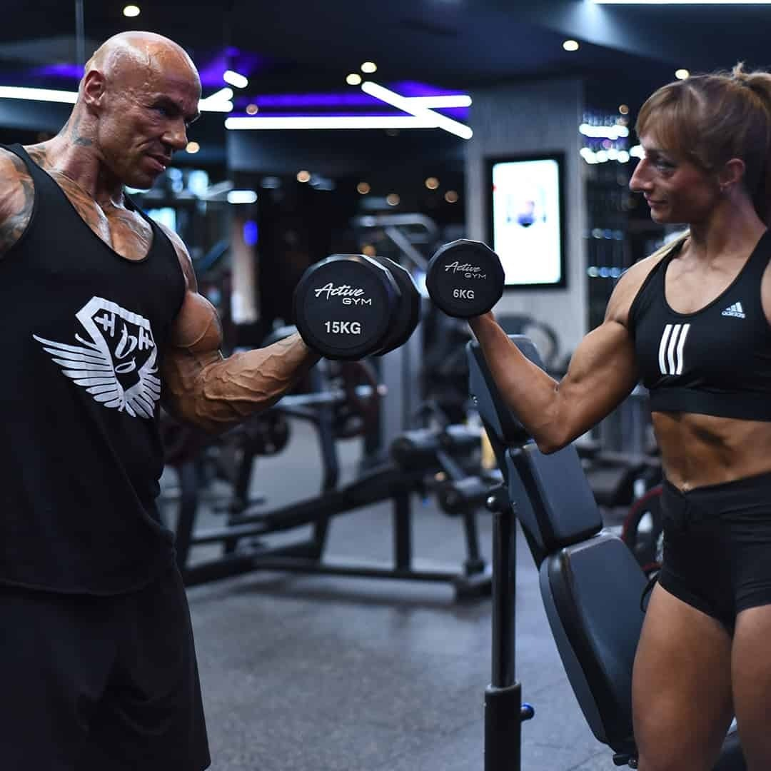 Tose Zafirov in a black t-shirt and black shots, lifting weights in the Pulse Fitness Center, together with his wife Gabriela Zafriova. She is wearing black adidas sports bra and black shorts.
