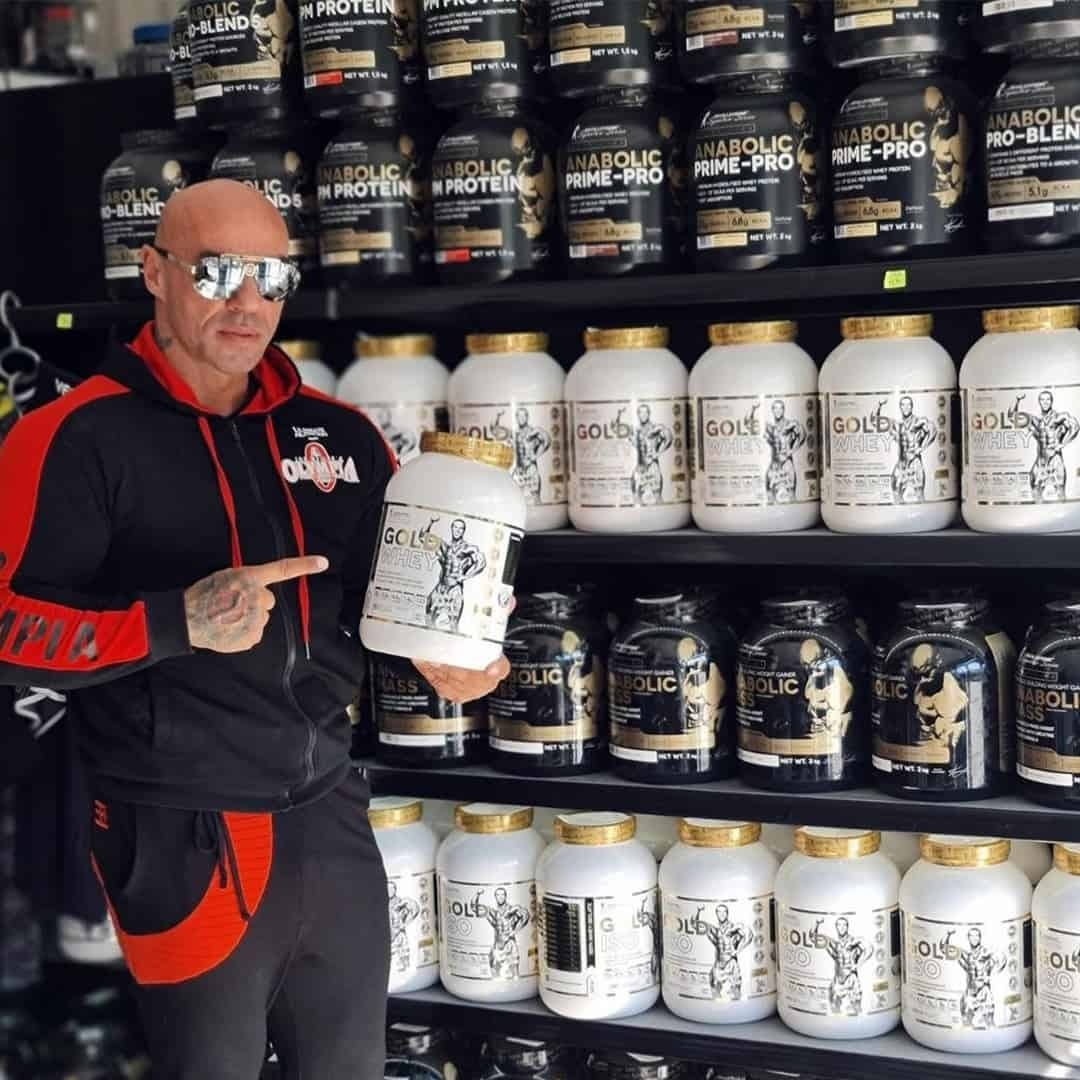 Tose Zafirov in a black suit track with red details, with sunglasses on his eyes, standing in front of a shelf with supplements from the Levrone Signature Series. He is holding one box of protein and he is pointing with his finger to it.