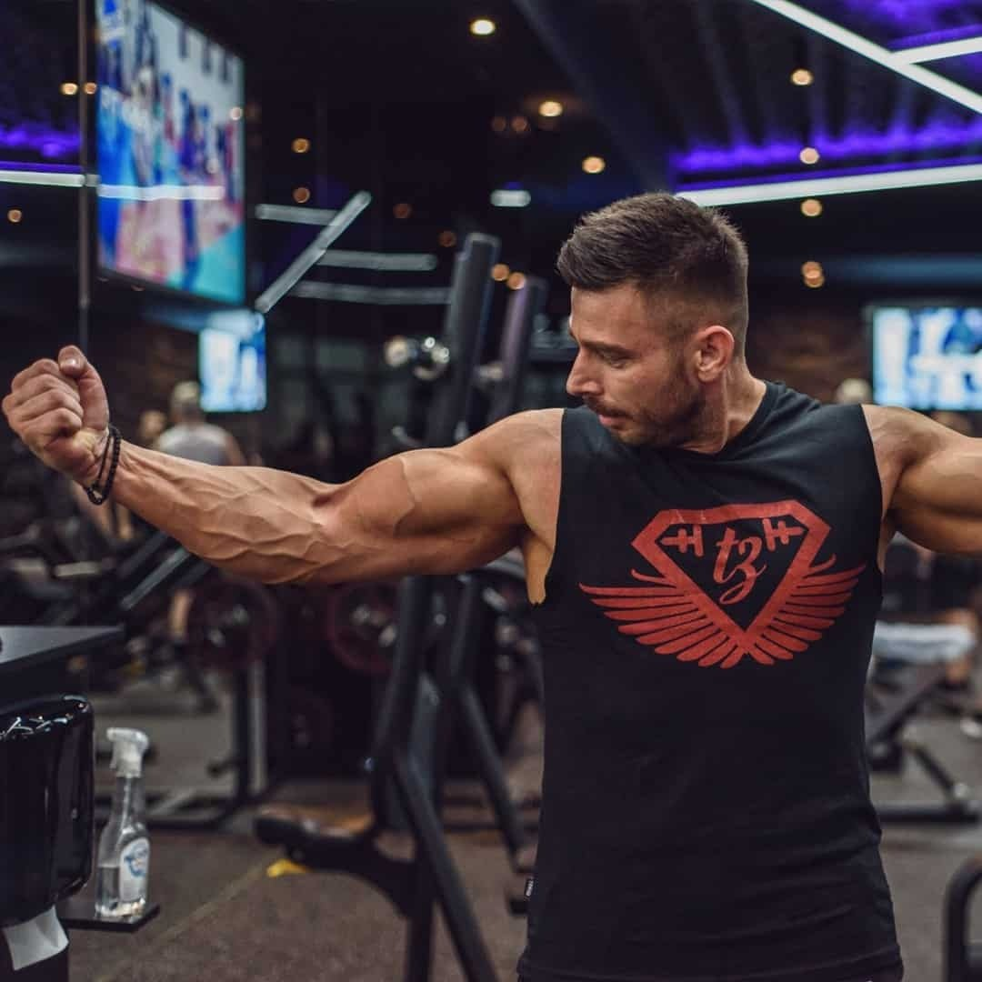 Trajche Stojanov Flexing his biceps at the gym while wearing black t-shirt with red details.