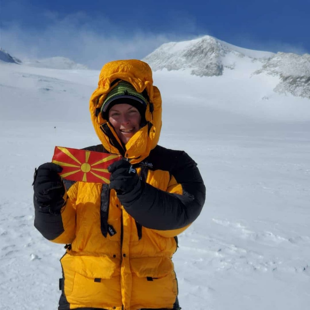 Ilina Arsova on the top of a mountain, with snow on it. She is holding the Macedonian flag in her hands, and she is wearing winter suit in black and yellow color.