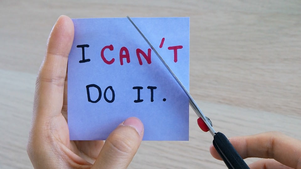 """An image of a person about to cut a blue not that says """"I can't do it"""" so it can say """"I can do it"""""""