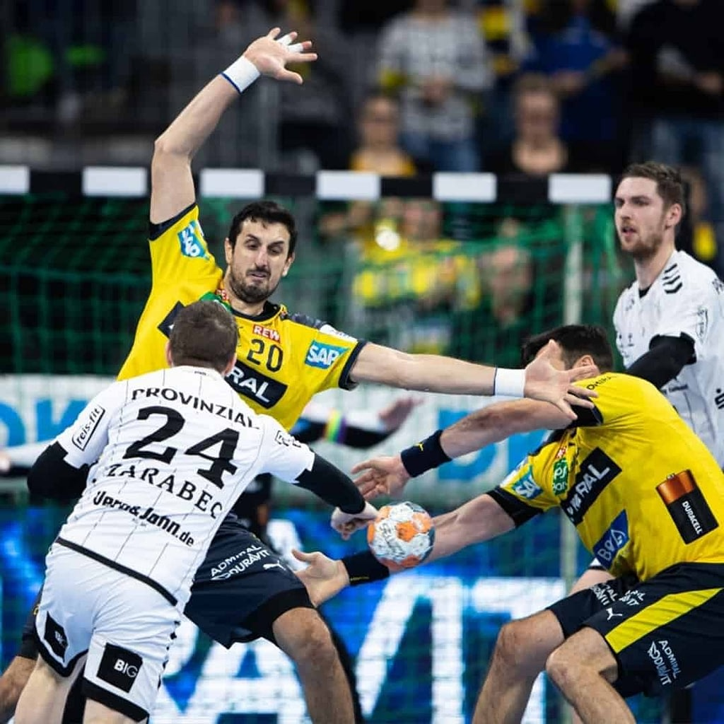 Ilija Abutovic in yellow jersey playing handball at a tournament, together with another player from his team , and two other players, in a white jerseys, from the opposite team.