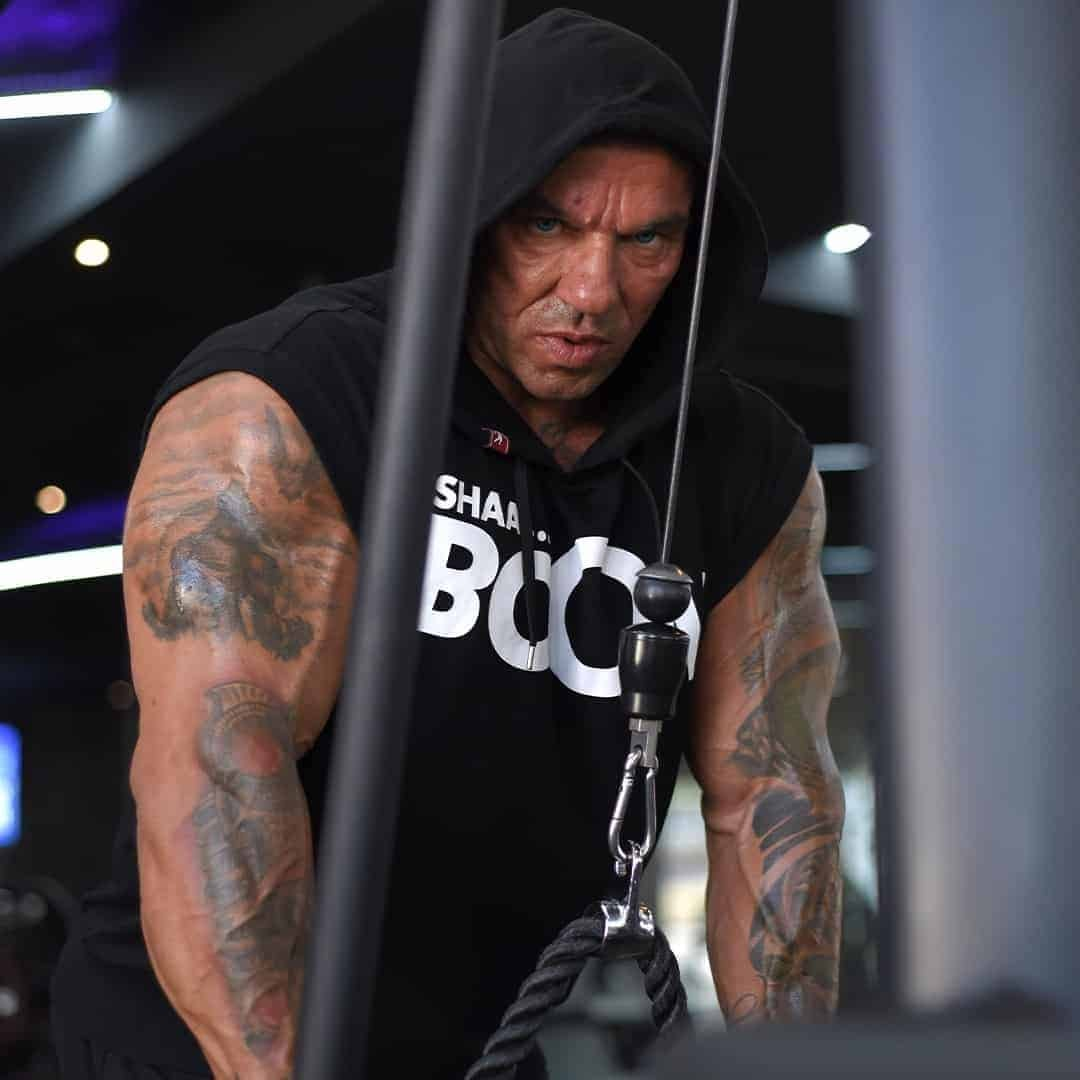 Tose Zafriov in a black t-shirt, with the hood on his head, staring furiously in the camera while ding exercise.