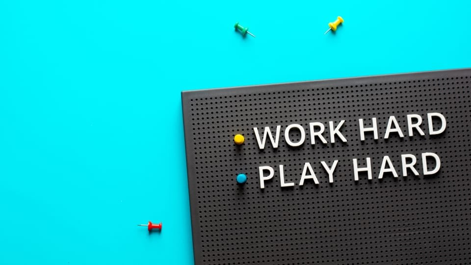 """An image with a blue background and a blackboard where we have the words """"work hard"""" and """"play hard"""" pinned"""