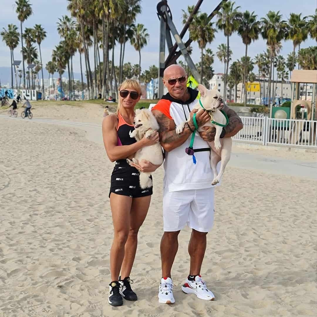 Tose Zafirov and Gabriela Zafirova standing one to another on the beach in California, with palms in the background. Gabriela is wearing black, Nike sports bra with orange details, black shorts with white details, and sunglasses on her eyes. She is holding white little dog. Tose is wearing white t-shirt with orange details, white shorts, and sunglasses on his eyes. Tose is holding white French bulldog.