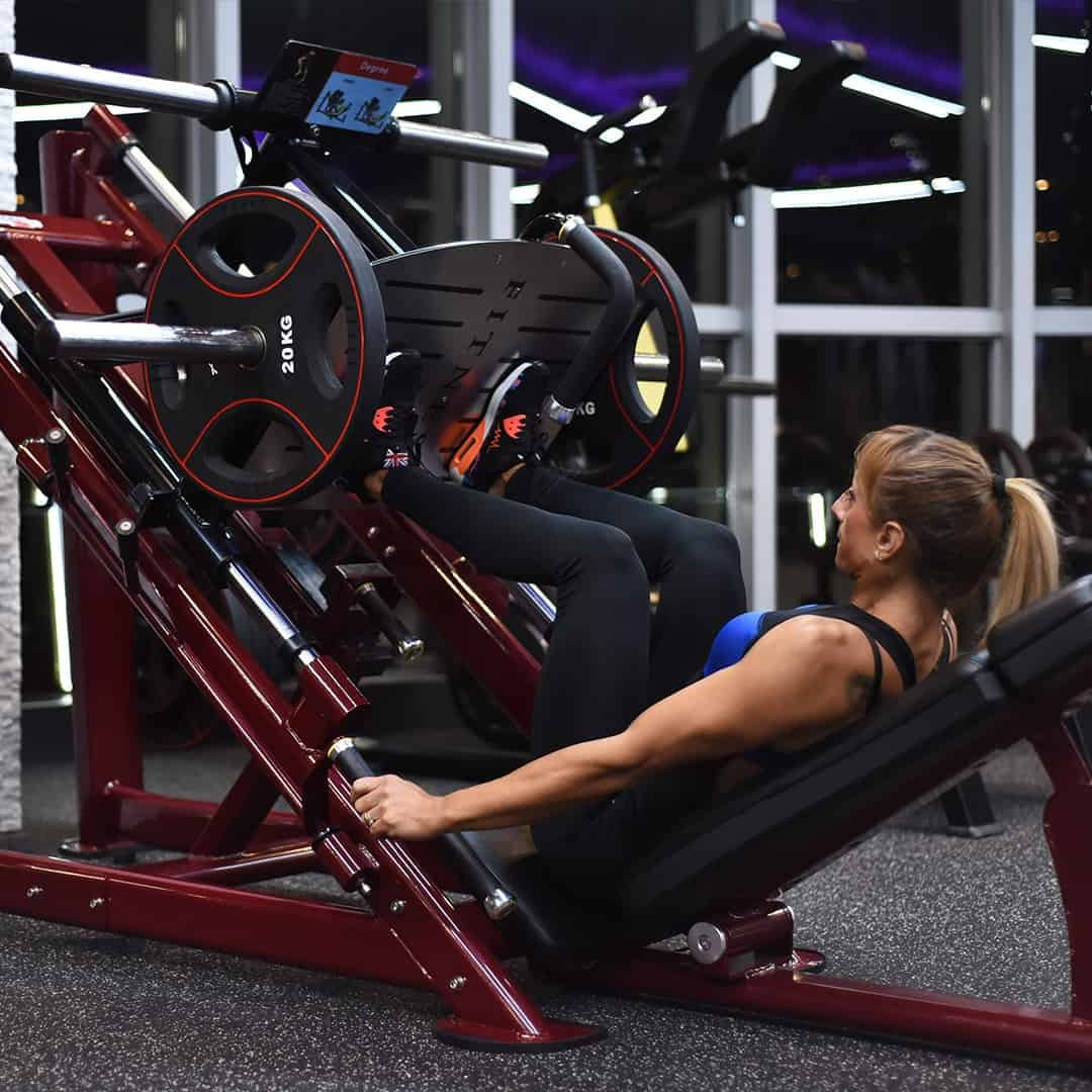 Gabriela Zafirova training her legs at the gym pulling hard weights up. She is wearing black leggings and black sports bra with navy blue details.