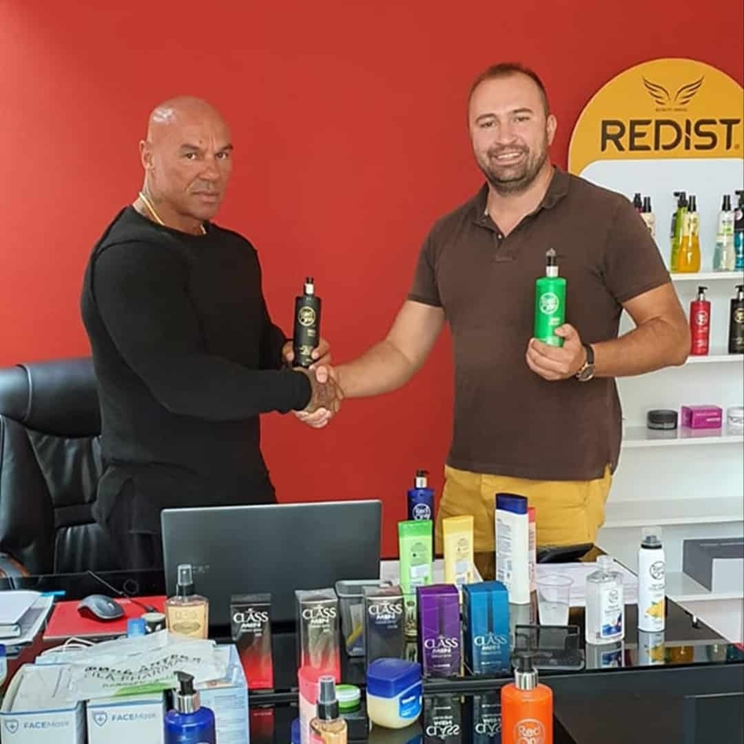 Tose Zafirov Next to the Founder of the Cosmos Group, shaking their hands and they are both holding Redist product. There is a red wall behind them, and some products in front of them.