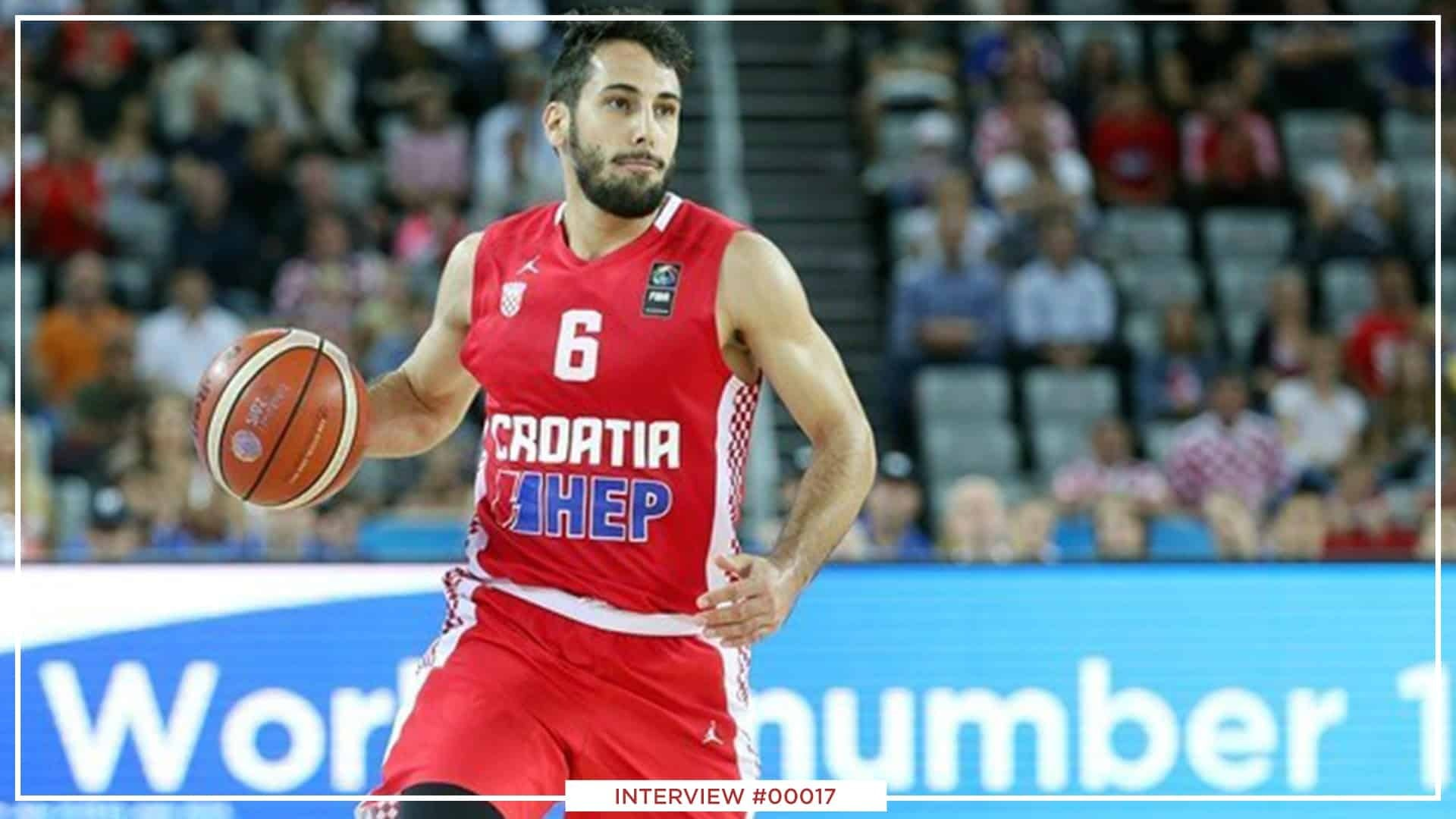 Rok Stipcevic wearing a red jersey and holding a basketball.