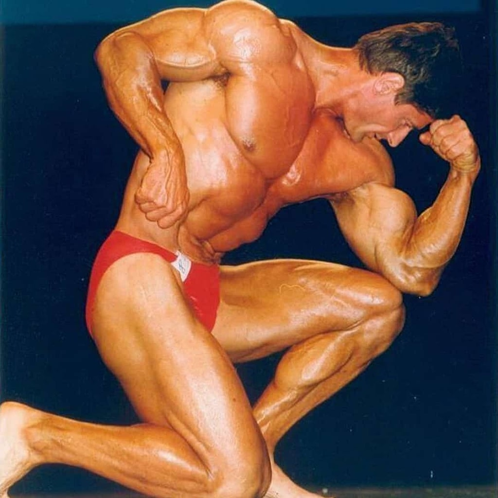 Petar Celik at his prime flexing his muscles on the stage and wearing red trunks.