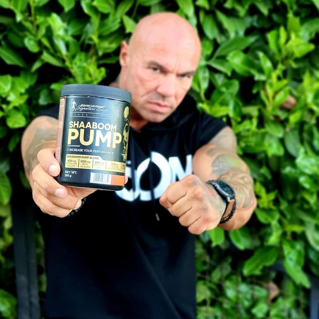 Tose Zafirov on green background, while holding Shaaboom Pump pre workout. He is wearing black t-shirt.