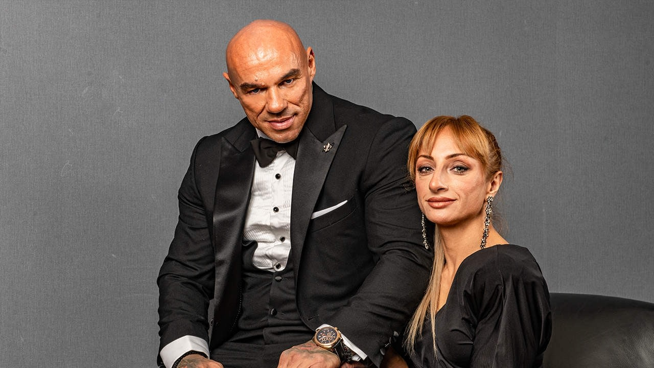Tose Zafirov in black suit with white shirt, elegant vest and black bow tie from Signori, with a black watch on his hand, with his wife Gabriela Zafirova sitting next to him, wearing black dress and smiling at the camera.