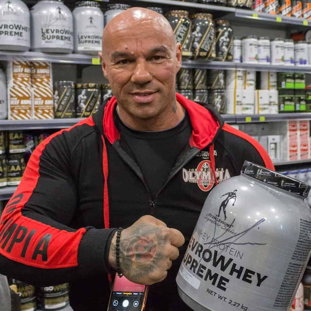 Tose Zafriov, in a black Mr. Olympia hoodie, holding whey protein front the Levrone Signature Series. He is standing in front of a shelf with suplements,