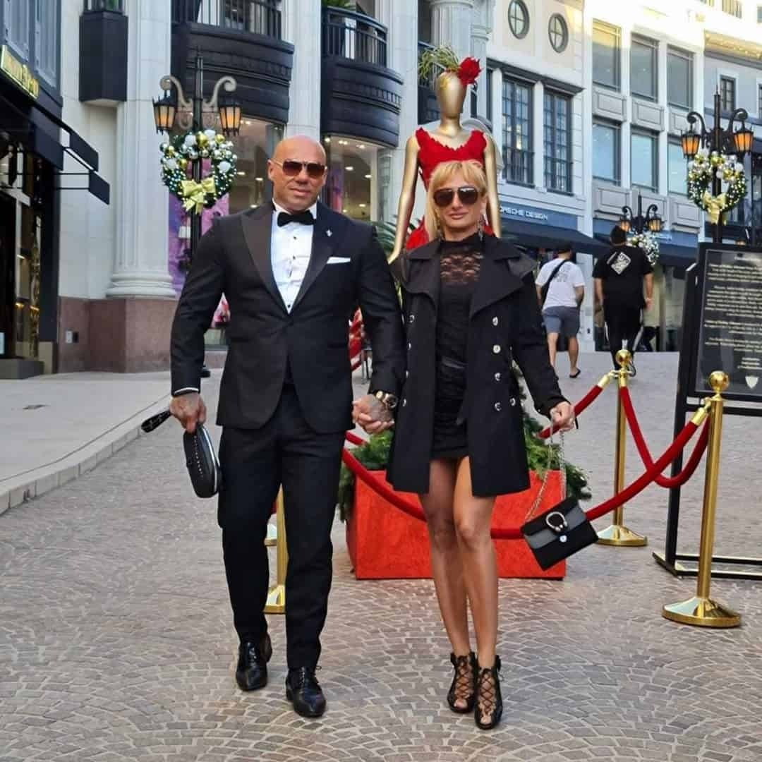 Tose Zafirov in a black Signori suit, with white shirt , and black bow tie, with sunglasses on his eyes, next to Gabriela Zafirova. Gabriela is wearing black short, black dress and coat, and sunglasses. They ae holding their hands, while walking on the street in Beverly Hills.