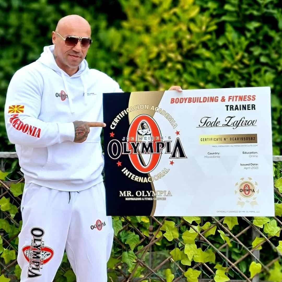 An image of Tose Zafirov holding his Mr. Olympia Certificate for Bodybuilding and fitness trainer. He is wearing white Mr. Olympia tracksuit, and sunglasses on his eyes.