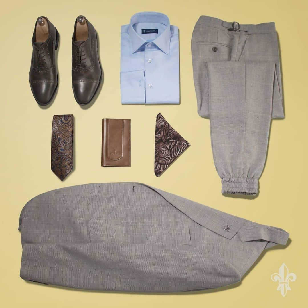 An image of an entire Suit setup from Signori . There are trousers, and suite in a light grey colour, shirt in a blue colour, dark brown shoes, brown tie with navy blue details, and brown handkerchief with white details. All those things on a yellow background.