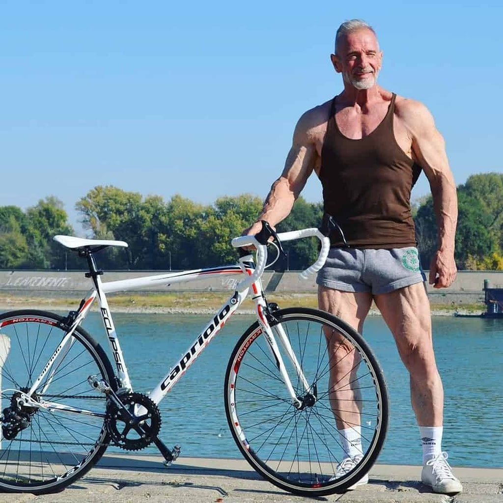 An image of Petar Celik, standing next to his bike near a river in a brown t-shirt and grey shorts, wearing white shoes.