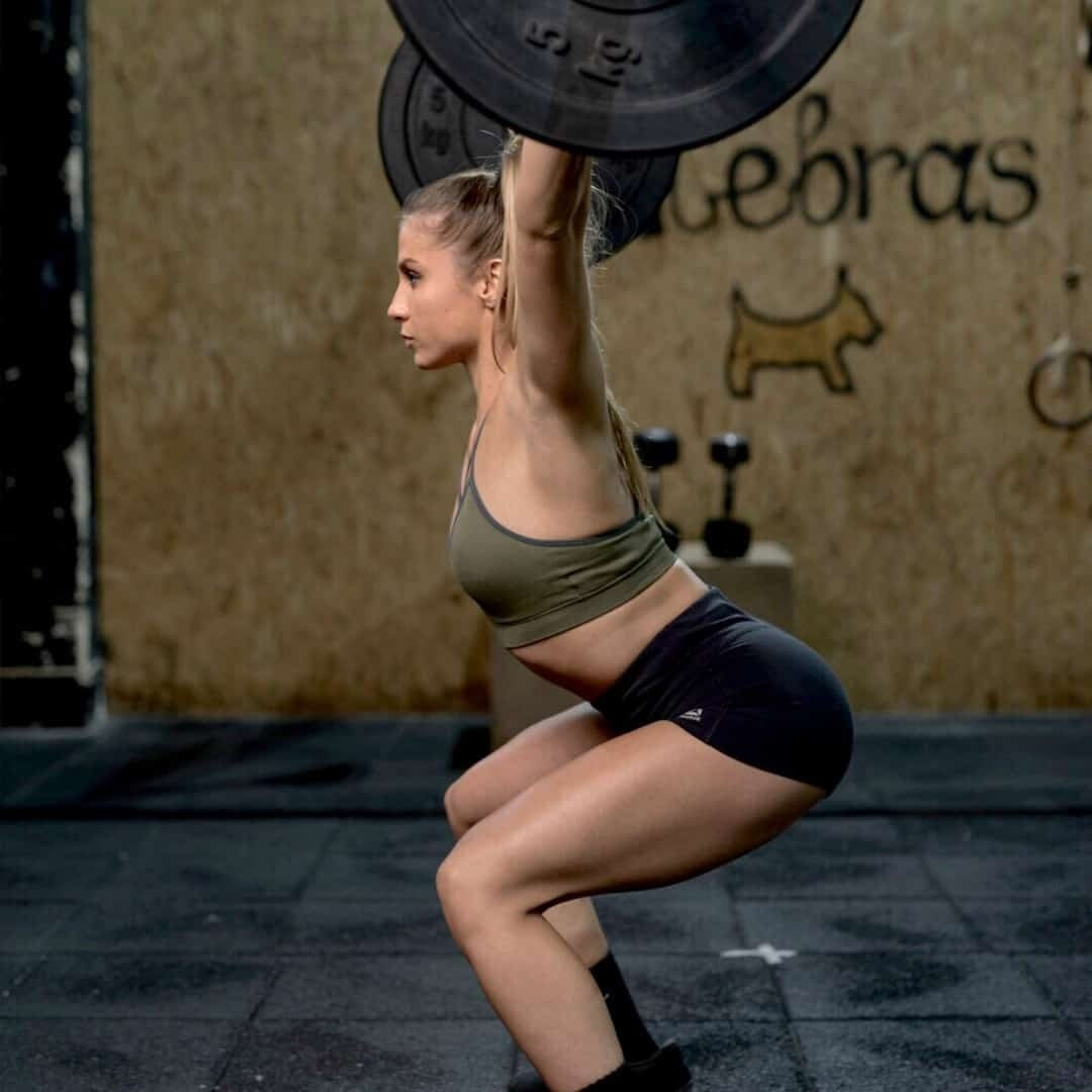 An image of Silvana Veljanoska holding weights over her shoulders in a squatting position. She is wearing black shorts and green sports bra.