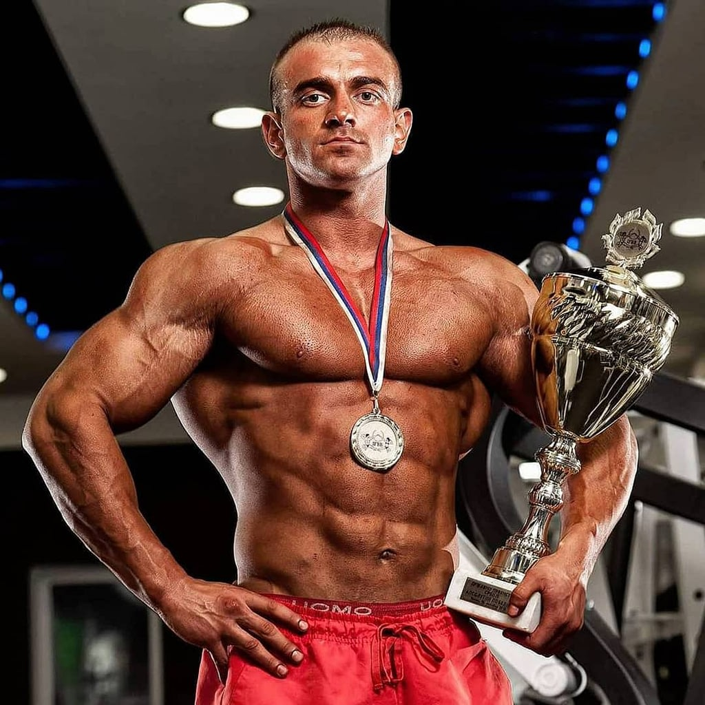 An image of Lepomir Bakic, a famous, professional bodybuilder. He is holding a trophy in one hand, while his other is on his hip. He also has a medal on his neck. He is shirtless, wearing red shorts, looking straight at the camera.