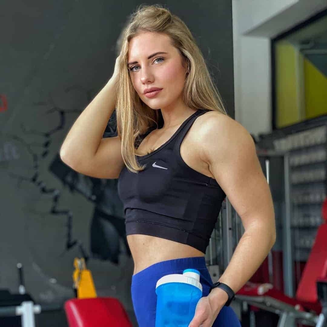 Sara Stojanoska at the gym posing for the camera while holding a blue bottle in her hands. She is wearing navy blue sports bra and blue pants.