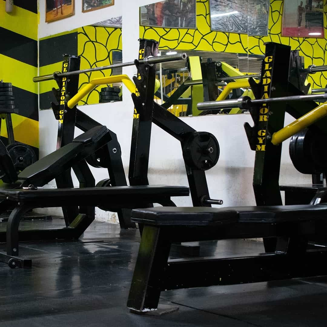 Tose Zafirov Fitness Center image showcasing the gear through which bodybuilders can train in black and yellow, specifically the bench presses