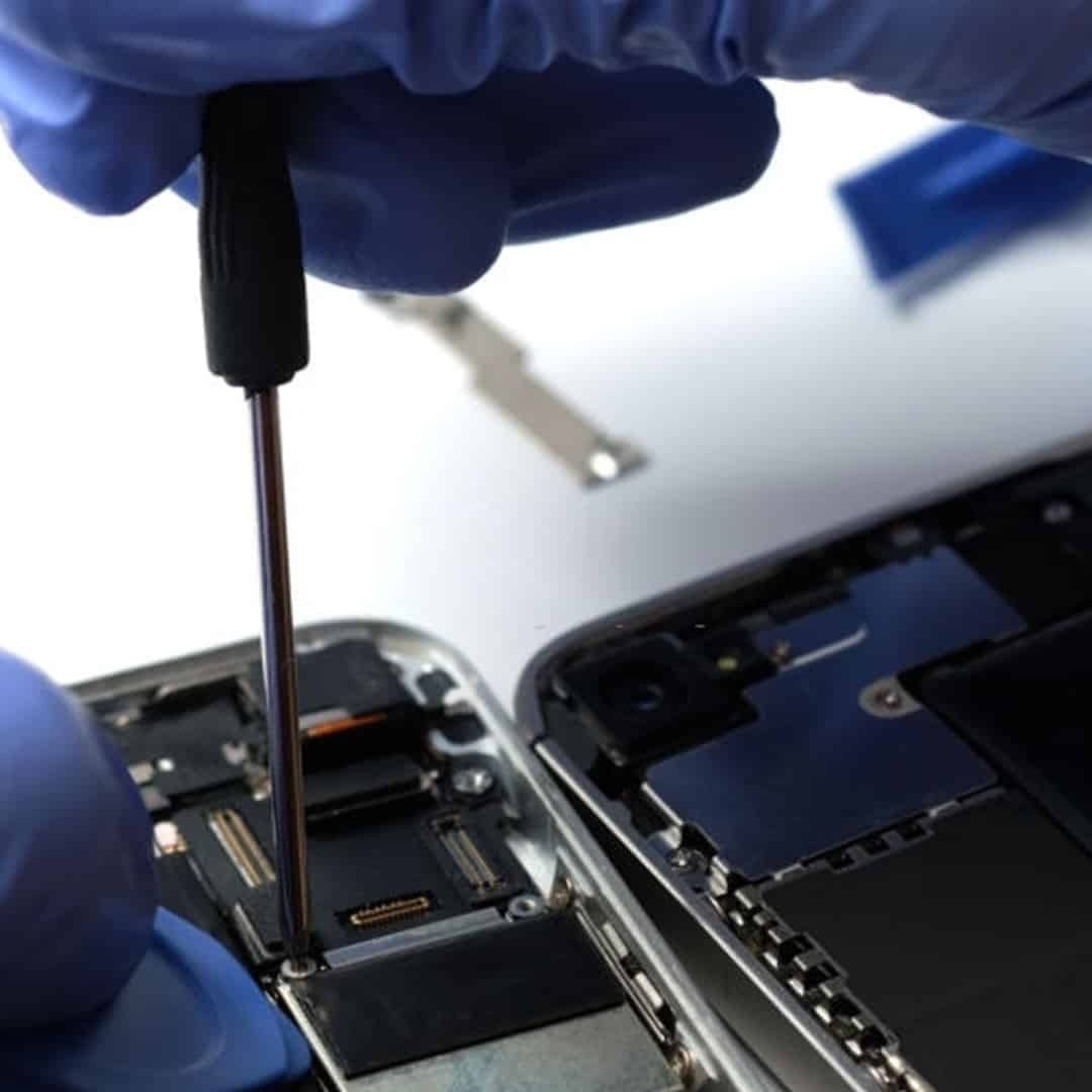 An image of hands with blue medical gloves, repairing a phone