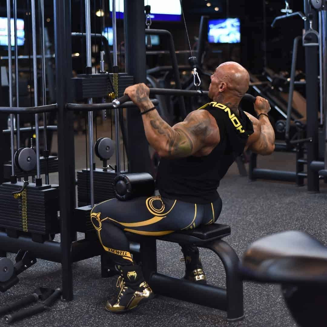 Tose Zafriov in a black t-shirt with hood, and black leggings, both with yellow details, doing chest exercise in the gym.