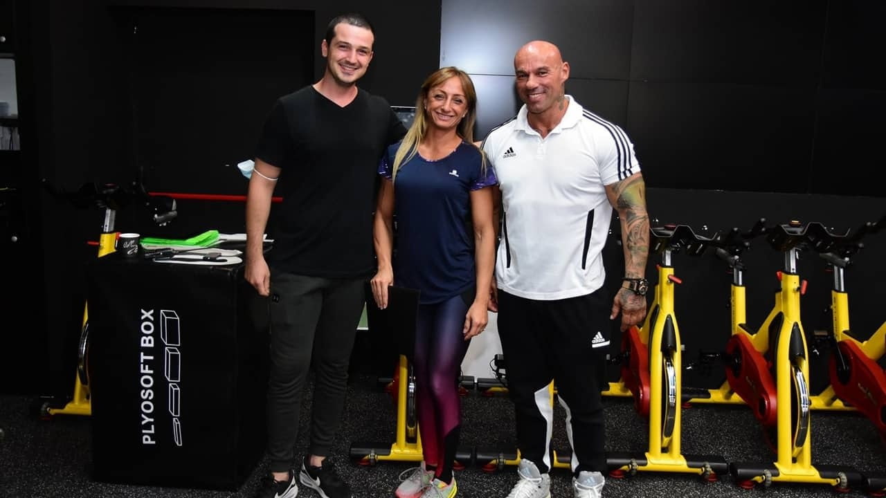 Tose Zafirov in a white, adidas t-shirt and black sweatpants. He staying next to Gabriela Zafirova, together with Josif Damjanov. They are all smiling in front of the camera.