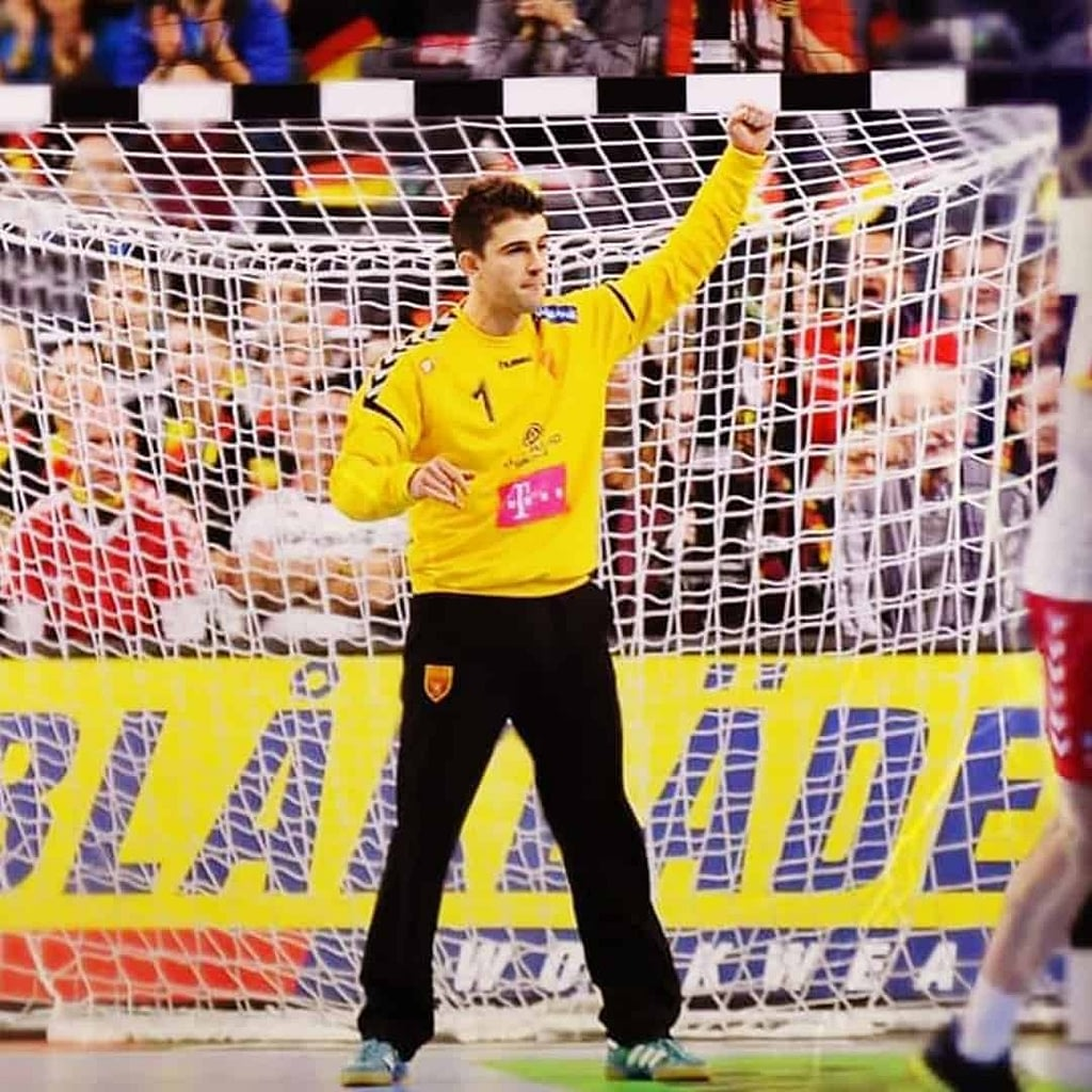 Nikola Mitrevski in front of the goal during a match, with his hand up. He is wearing yellow jersey and black sweatpants.