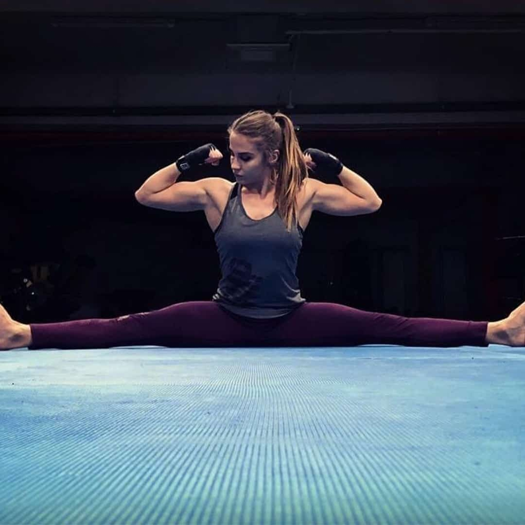 Silvana Veljanoska flexing her muscles both in terms of hands and in legs while doing sword. She is wearing grey t-shirt and purple leggings.