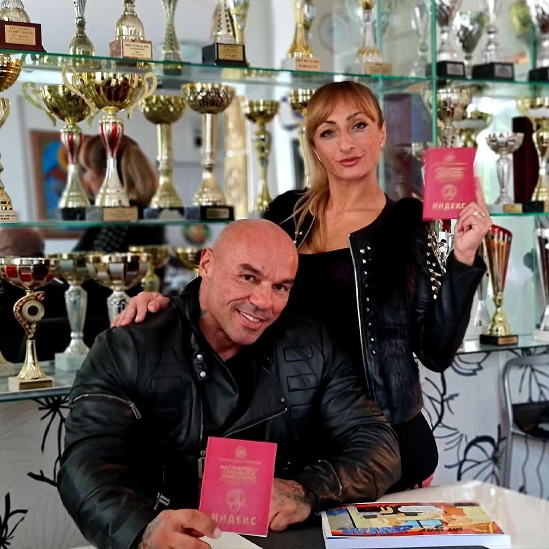 Tose Zafirov in a black, leather jacket, sitting on a chair in front of a shell with his medals and holding his university index while his wife, Gabriela Zafirova is standing next to him, wearing black leather jacked and holding her university index.