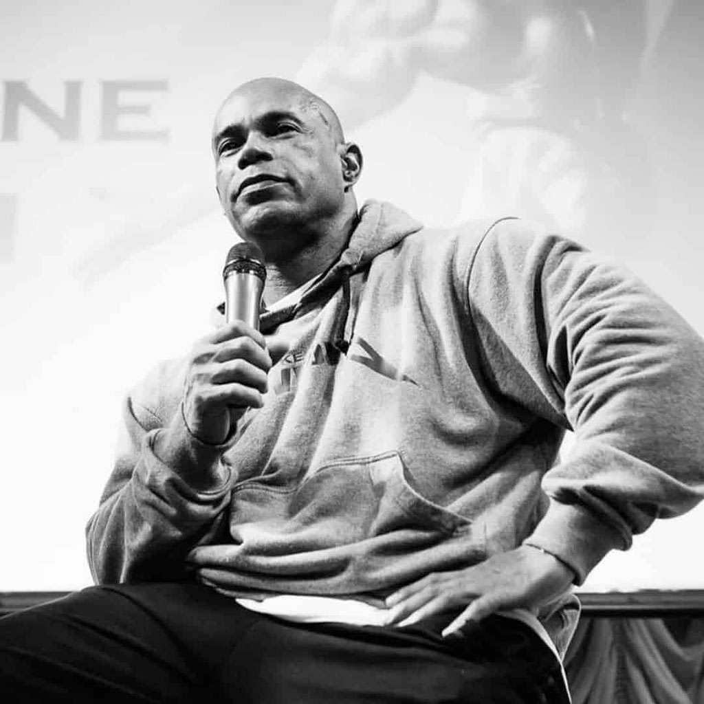 A picture of Kevin Levrone in black and white where he is publicly speaking at an event where he sitting in front of an audience.