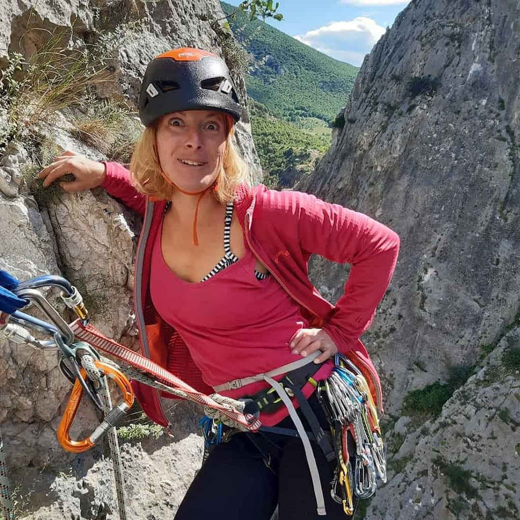 Ilina Arsova while hiking on a mountain. She is wearing protctive hat on her head, pink blouse and some security bells.