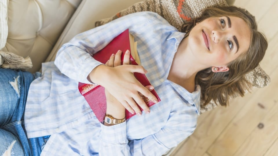 A woman lying on the sofa and holding her book on the chest after reading something spectacular. She is wearing shirt and jeans, and she is smiling.