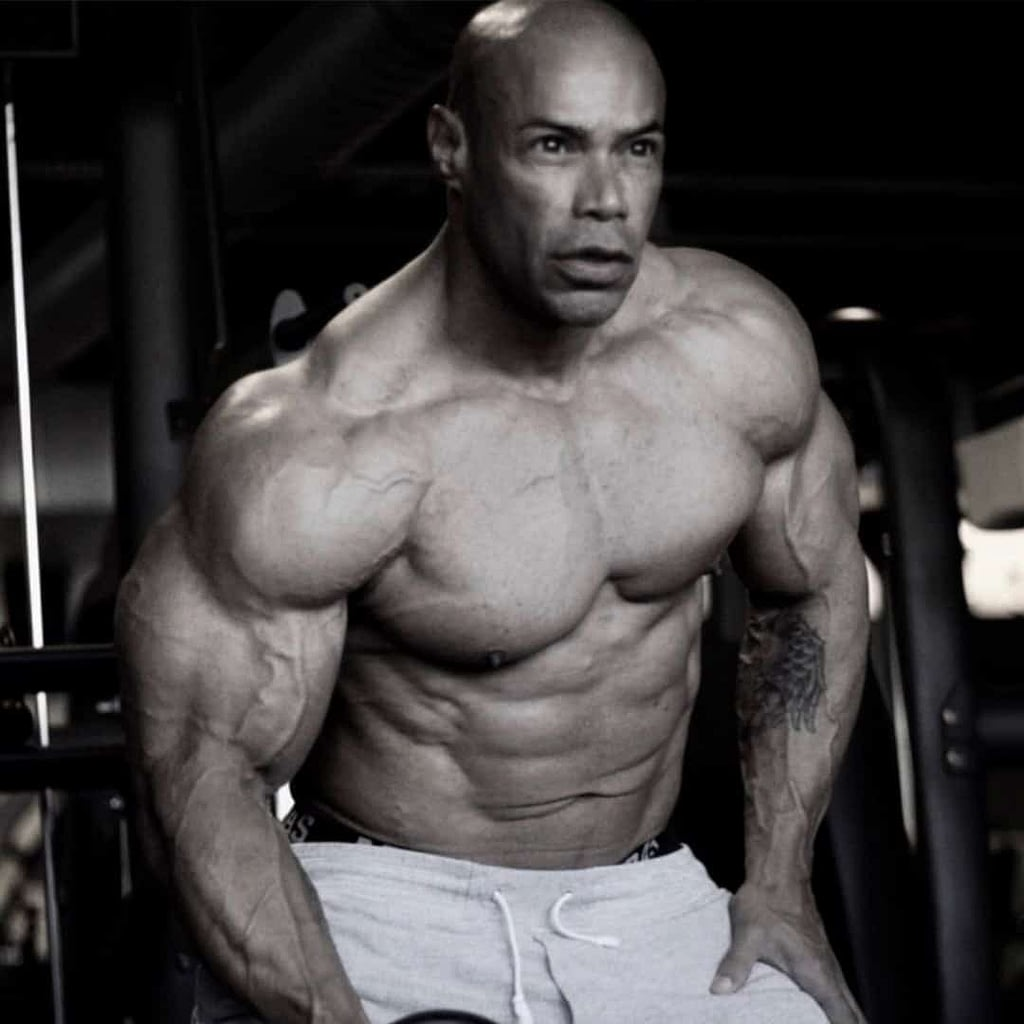 An image of Kevin Levrone flexing his muscles at the gym after a workout. He is not wearing a t-shirt.