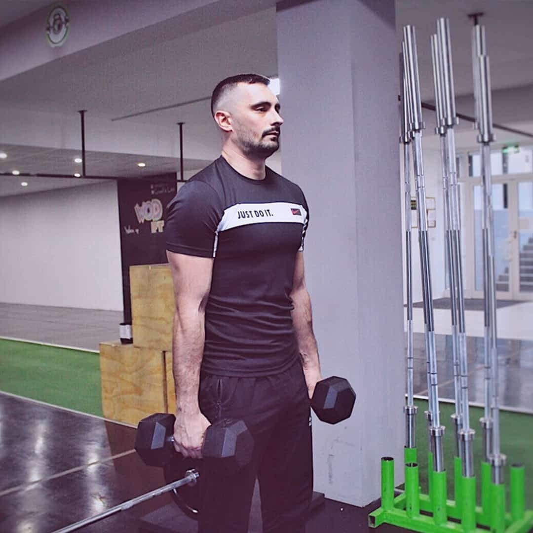 Aleksandar Mandzukovski training his shoulder muscles by holding two weights. He is wearing black t-shirt with white details, and black sweatpants.