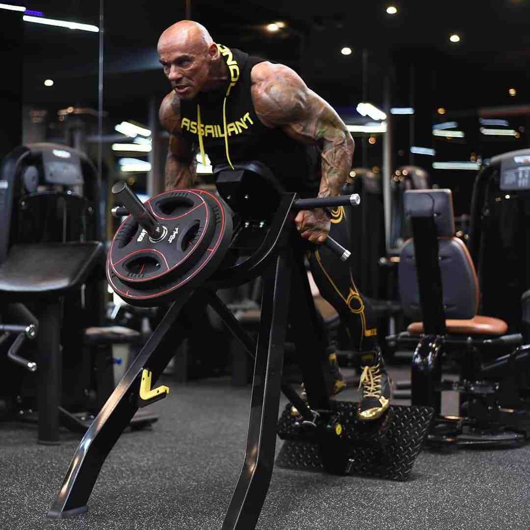Tose Zafriov in a black t-shirt with hood, and black leggings, both with yellow details, doing exercises for this back in a gym.