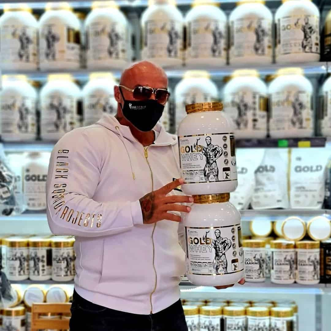Tose Zafirov in a white hoodie with gold details, and sunglasses on his eyes, and mask, standiing in front of a shell with supplements from the Levrone Signature Series.
