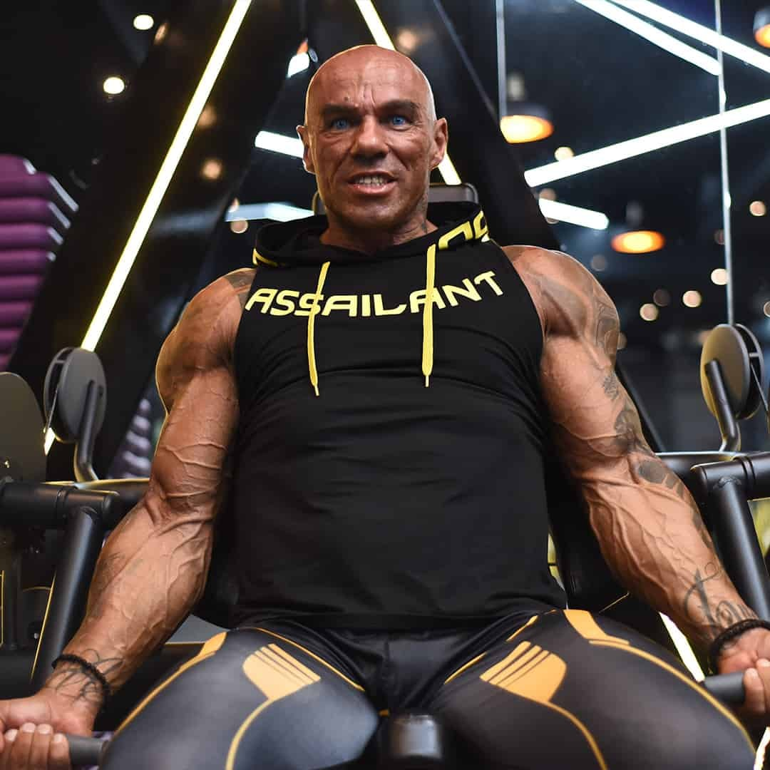 Tose Zafirov training his bicep muscles at the gym while staring furiously at the camera. He is wearing black t-shirt and leggings with yellow details,