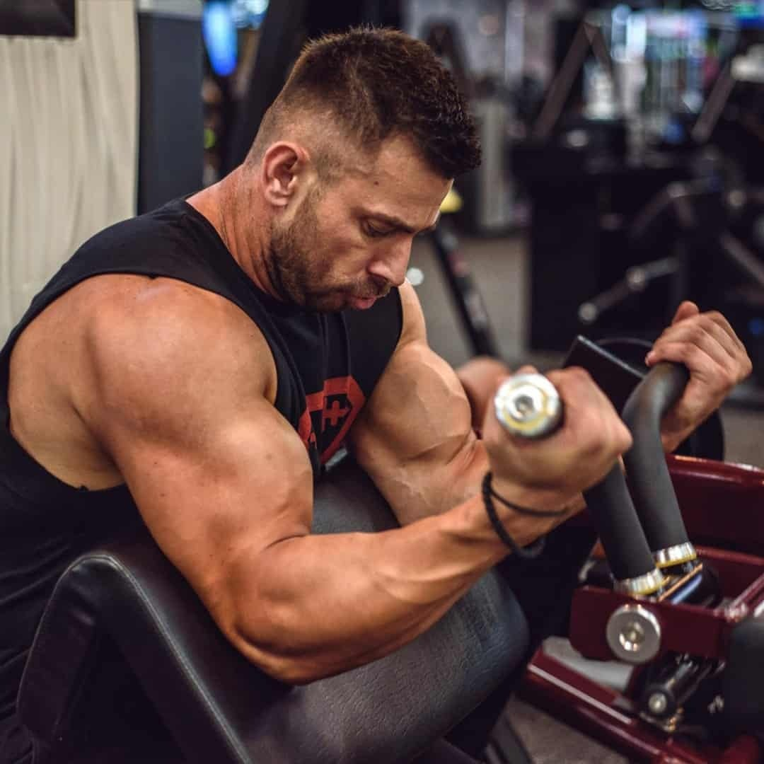 Trajche Stojanov training his biceps on a machine at the gym, while wearing black t-shirt wit red details.