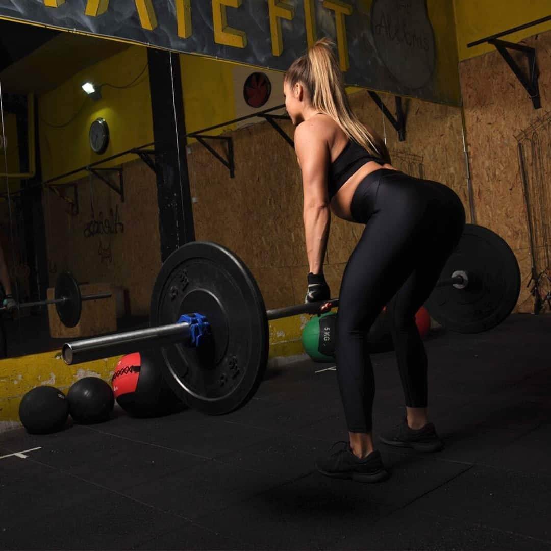 An image of Silvana Veljanoska making a deadlift exercise within a gym. She is wearing black leggings and black sports bra.
